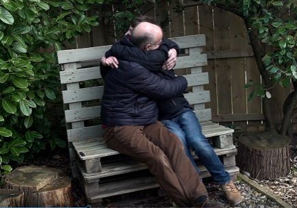 Ian and Mark Blakemore hugging on a bench