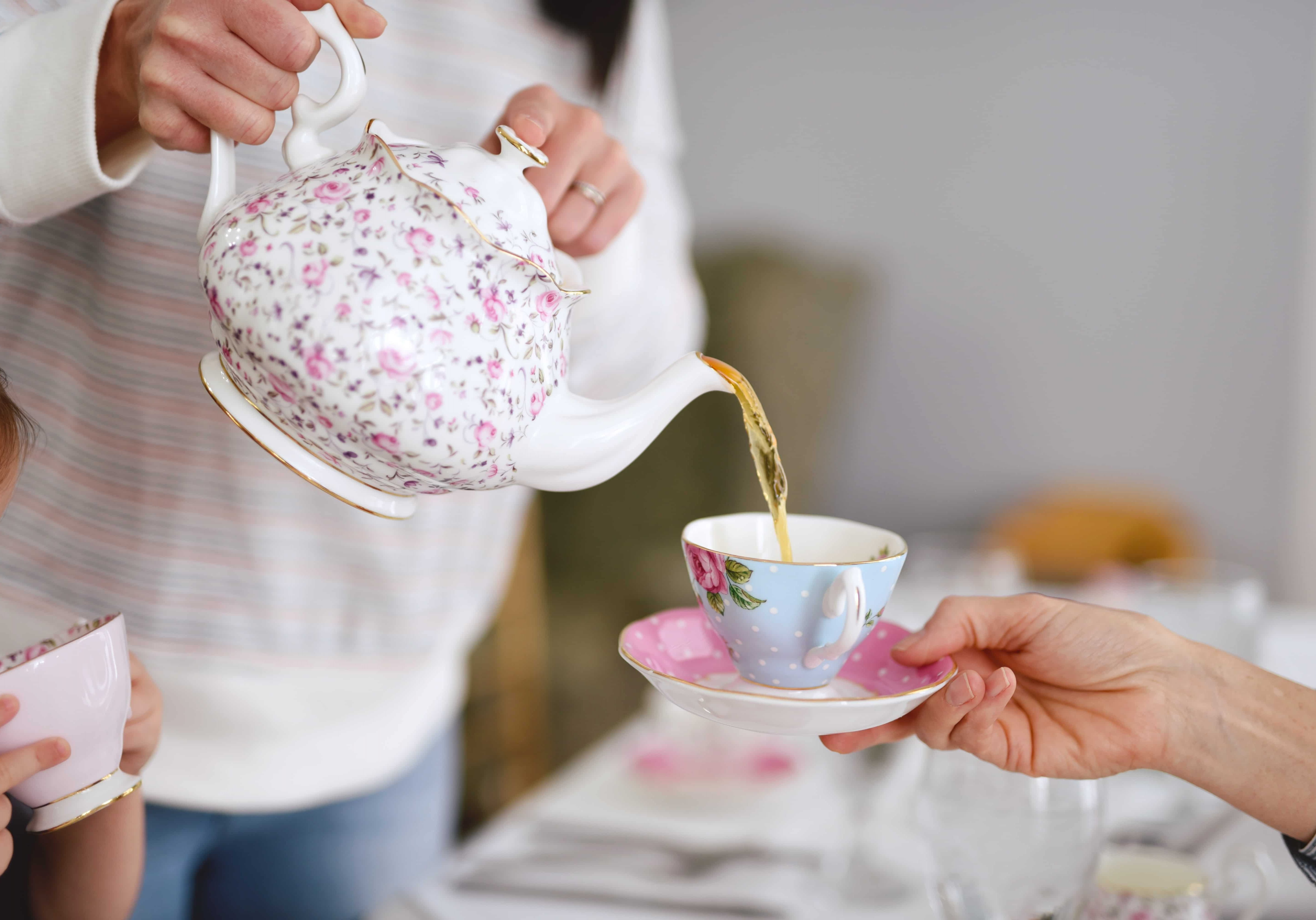 Hand pouring tea from a teapot into a cup and saucer